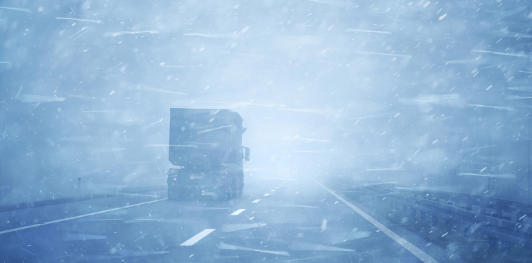 Concept truck vehicle at highway road during a heavy snowfall and rainfall.