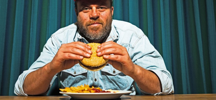 Man with beard and red cap eating fast food meal.