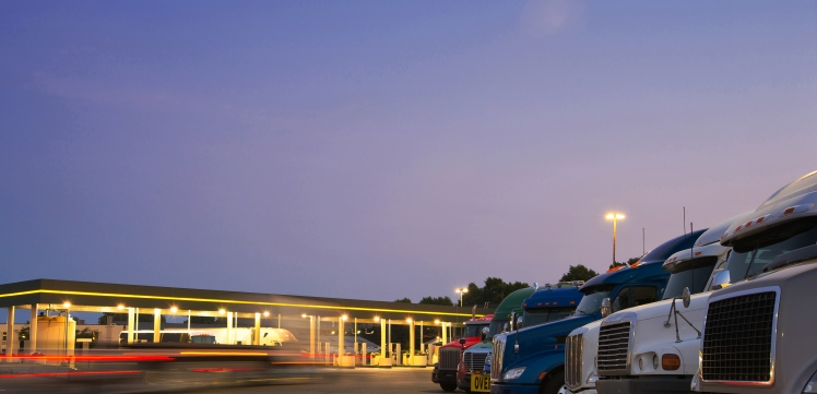 Evening truck stop lights of number of trucks in parking